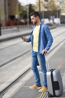 Young man waiting at a station with smartphone in his hand and trolley - JSMF00155