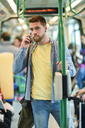 Young man in a subway train using his smartphone - JSMF00161