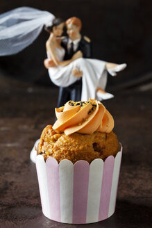 Carrot cup cake garnished with  cream topping, sugar granules and marzipan carrot - CSF29183