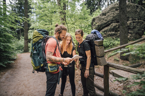 Friends on a hiking trip reading map - GUSF00723