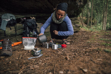 Young woman on a trekking tour preparing drinks - GUSF00732
