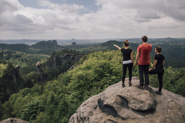 Germany, Saxony, Elbe Sandstone Mountains, friends on a hiking trip standing on rock - GUSF00735