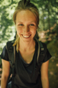 Portrait of smiling young woman on a hiking trip - GUSF00741