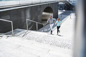 Couple running on stairs in the city - DIGF04035