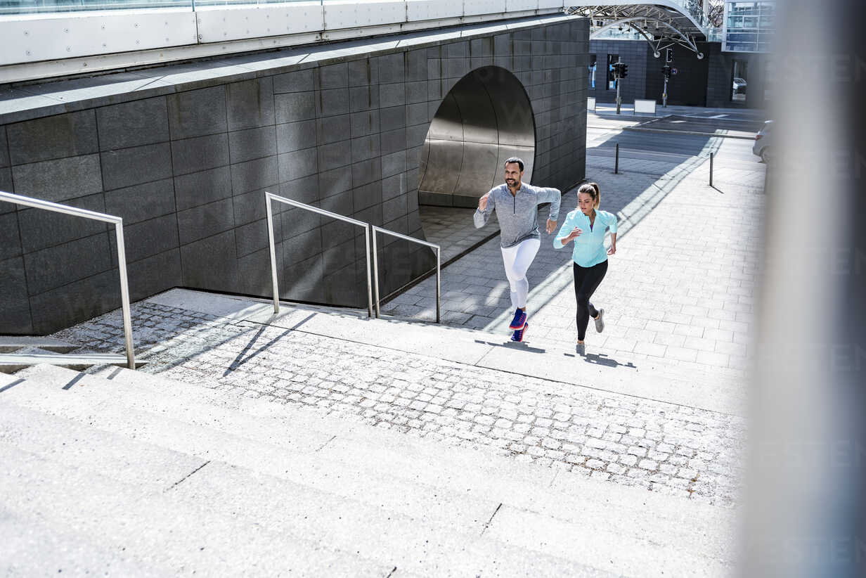 Couple running on stairs in the city - DIGF04035 - Daniel Ingold/Westend61