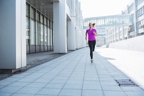 Young woman running in the city - DIGF04050