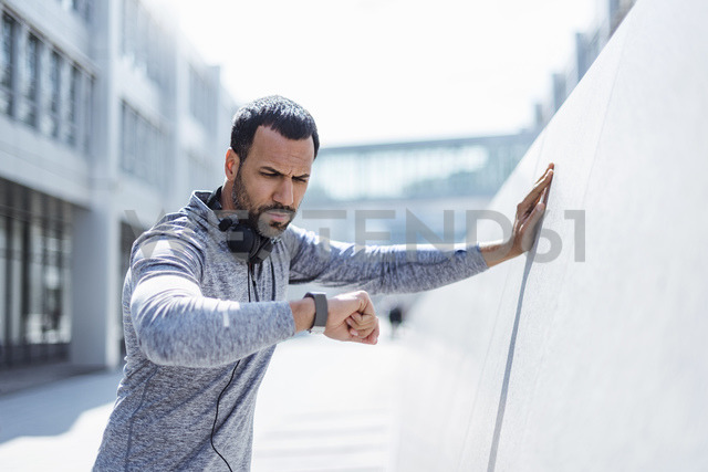 Man having a break from exercising looking on smartwatch - DIGF04053