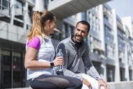 Active couple with water bottle having a break in the city - DIGF04062