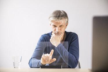 Mature businessman using transparent touchscreen computer - FMKF05030