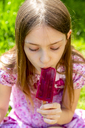 Portrait of girl eating popsicle in garden - SARF03701