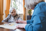 Woman taking care of old woman doing crossword puzzle - DIGF04071
