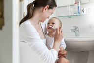 Mother brushing baby's teeth in bathroom - DIGF04074