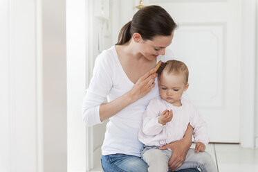 Mother brushing baby's hair at home - DIGF04077