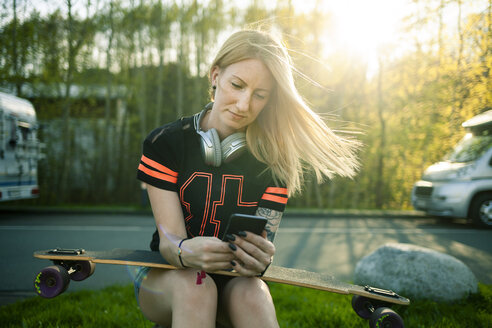 Portrait of blond woman with longboard sitting at roadside using smartphone - NAF00088