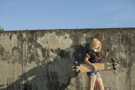 Blond woman with longboard standing in front of wall looking at smartphone - NAF00091