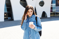 Spain, Barcelona, smiling young woman using cell phone and earphones outdoors - VABF01552