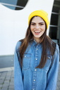 Portrait of laughing young woman wearing yellow cap - VABF01555