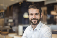Portrait of smiling young businessman in a cafe - DIGF04082