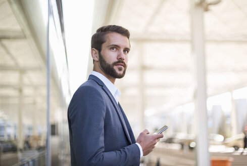 Young businessman holding cell phone looking sideways - DIGF04085