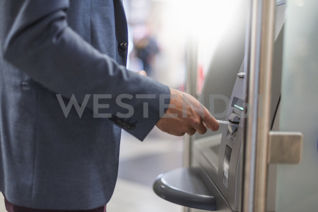 Close-up of businessman withdrawing money at an ATM - DIGF04088 - Daniel Ingold/Westend61
