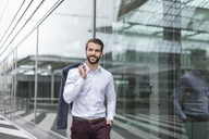 Portrait of smiling young businessman at glass facade - DIGF04103