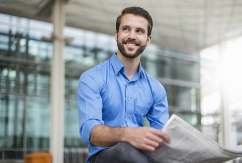 Smiling young businessman sitting outdoors with newspaper - DIGF04118