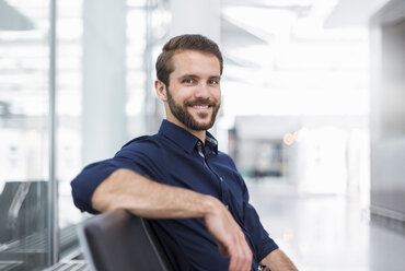 Portrait of smiling young businessman sitting in waiting area - DIGF04124