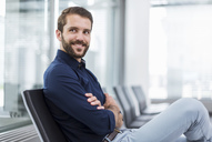 Smiling young businessman sitting in waiting area - DIGF04127