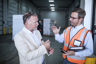 Businessman and man in reflective vest talking in industrial hall - ZEF15404
