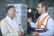 Businessman and man in reflective vest talking in industrial hall - ZEF15410