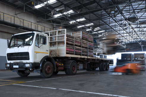 Forklift loading crates on parked truck in warehouse - ZEF15422