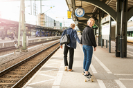 Young man pulling teenage girl on skateboard at railroad station platform - MASF07098