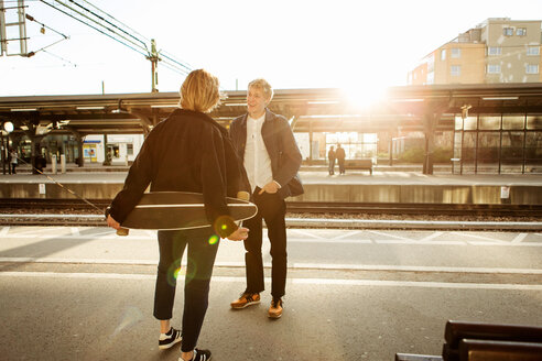 Happy young man talking with teenage girl while standing on railroad station platform - MASF07101