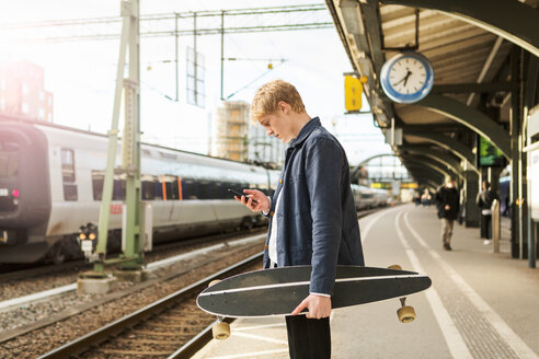 Side view of young man using mobile phone while holding skateboard on railroad station platform - MASF07104