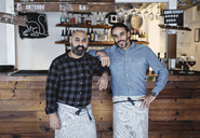 Portrait of male partners standing at bar counter - MASF07128