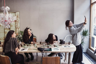 Smiling owner taking selfie with female coworkers sitting at table in perfume workshop - MASF07203