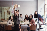 Smiling young woman taking selfie with female coworkers at table in workshop - MASF07206