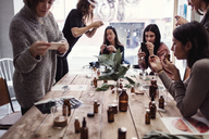 Multi-ethnic female coworkers photographing perfumes on table at workshop - MASF07209