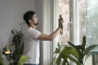 Side view of young man cleaning glass window in living room - MASF07254
