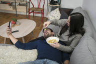 Happy man taking selfie while woman feeding chips to him on sofa - MASF07257