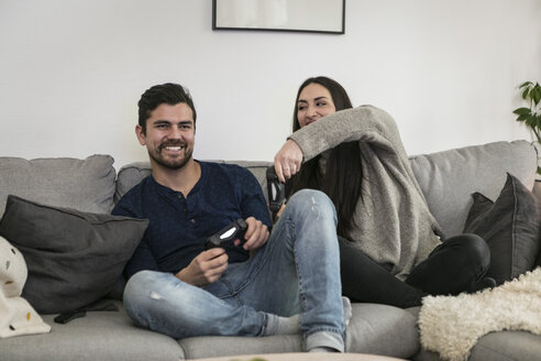 Happy couple enjoying while playing video game on sofa at home - MASF07260