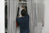 Rear view of man hanging clothes in closet at bedroom - MASF07269