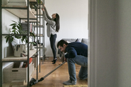 Man vacuuming floor while woman cleaning shelf at home - MASF07275