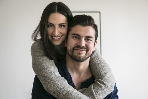 Portrait of affectionate smiling young couple standing against wall at home - MASF07281