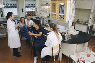 Full length of mature teacher explaining to young multi-ethnic university students sitting in chemistry laboratory - MASF07320