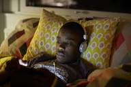 Close-up of boy with headphones using digital tablet while lying on bed at home - MASF07368