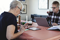 Senior couple using technologies while sitting at dining table - MASF07434