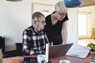 Senior couple with laptop at and financial bills at dining table - MASF07440