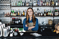 Portrait of smiling female owner standing with arms crossed at checkout counter - MASF07458
