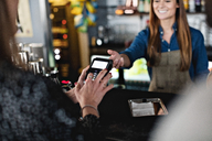 Female customer doing contactless payment to smiling owner at checkout counter - MASF07461